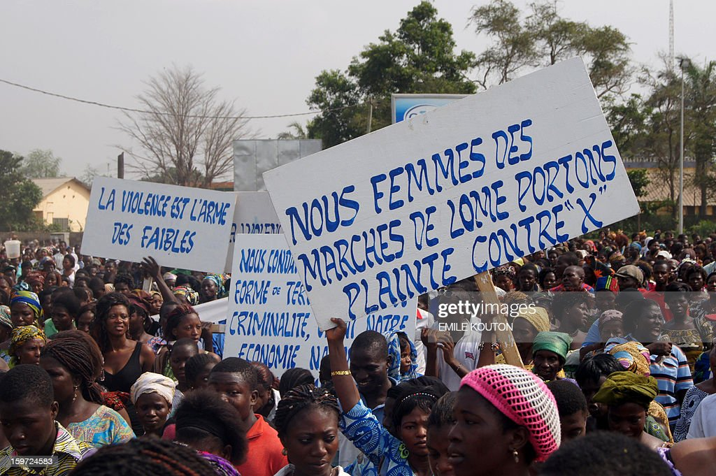 Supporters of the government protest in the streets of Lome on January 19, 2013 following fires of alleged criminal origin that ravaged two major markets in the country. Kara market some 420km north of the capital and the main building of Lome's largest market Adwalto were serverley damaged last week floowing the blazes. Placard reads, ' We women of the Lome Market file a complainte against X' AFP PHOTO / Emile KOUTON