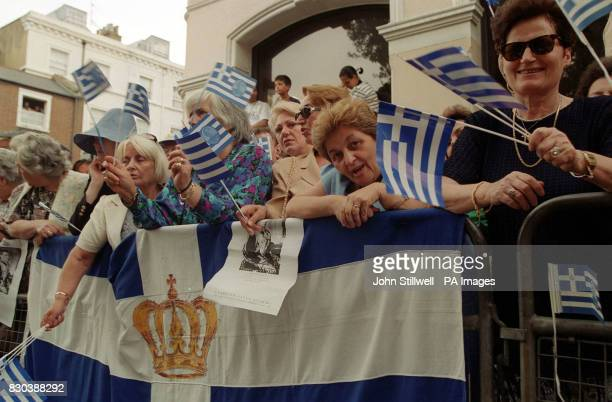 Supporters of the Greek royal family wave flags as they gather outside the Greek Orthodox Cathedral of St Sophia in Bayswater west London where the...