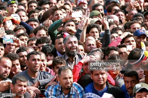 Supporters of the Iraqi Shiite cleric Moqtada alSadr react as he speaks during a demonstration in Tahrir Square central Baghdad on March 24 2017 The...