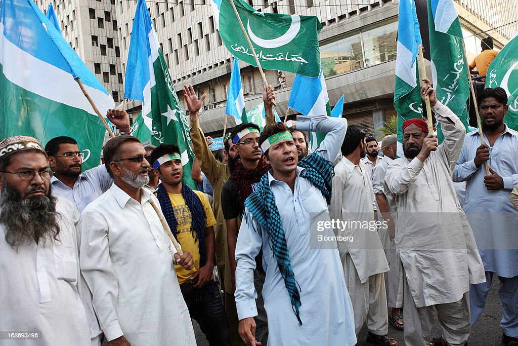 Supporters of the Jamaat-e-Islami (Islamic Party) wave flags and shout slogans during a demonstration in Karachi, Pakistan, on Monday, May 13, 2013. Nawaz Sharif was headed for a record third term as prime minister of Pakistan as unofficial results from a landmark election gave him the convincing win he sought to tackle a slumping economy and growing militancy. Photographer: Asim Hafeez/Bloomberg via Getty Images