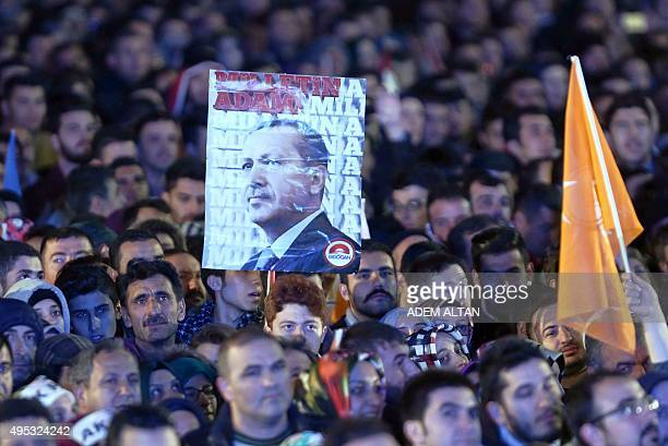 Supporters of the Justice and Development Party hold a banner of Turkish President Recep Tayyip Erdogan during a speech by Turkish Prime Minister...