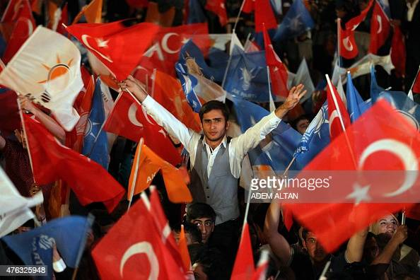 Supporters of the Justice and Development Party wave flags and shout slogans as the party's leader and Turkish Prime Minister delivers a speech from...