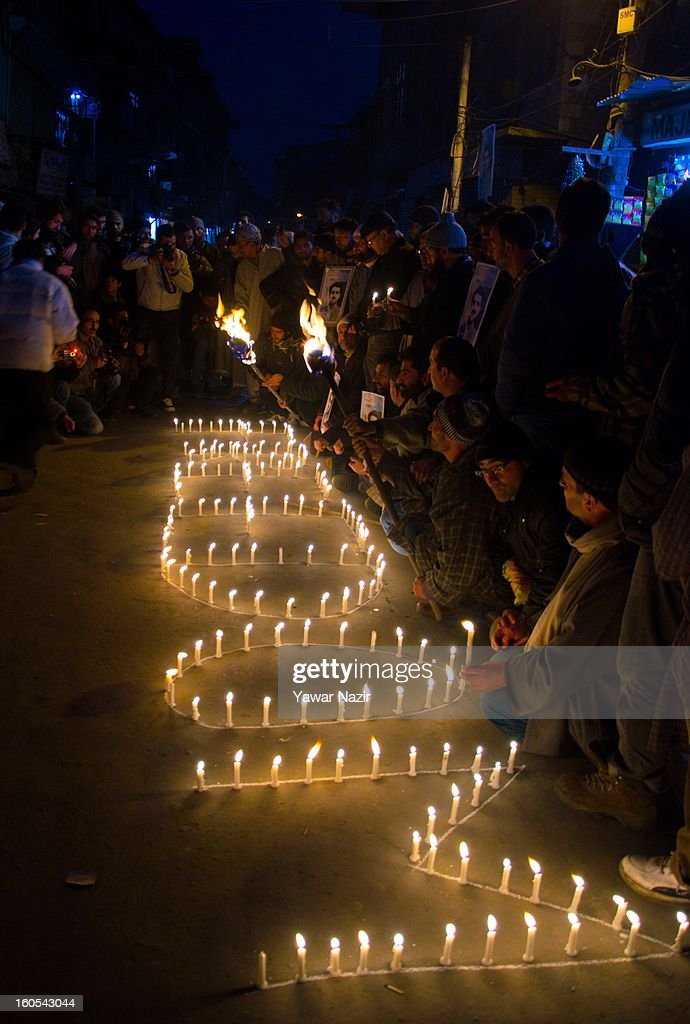 Supporters of the Kashmiri separatist party, the Jammu Kashmir Liberation Front (JKLF), assemble around an arrangement of candles spelling out 'Freedom' February 2, 2013 in Srinagar, the summer capital of Indian administered Kashmir, India. Members of the pro-independence JKLF carried banners and placards during a silent sit-in protesting death and life sentences handed down to Kashmiri prisoners by Indian courts.