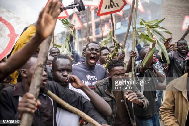 TOPSHOT Supporters of the Kenyan opposition presidential candidate shout and hold sticks during a protest in the Mathare slums of Nairobi on August 9...