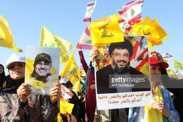 Supporters of the Lebanese Shiite movement Hezbollah hold a poster bearing a portrait of Hassan Nasrallah ahead of a speech by him to mark the 11th...