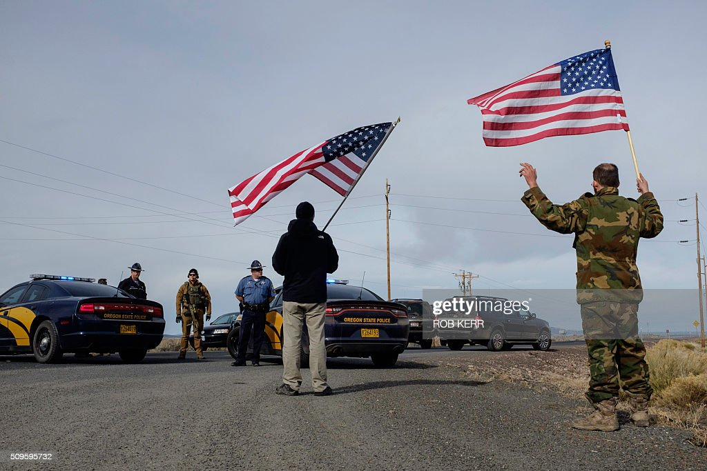 Supporters of the movement agains the federal government carry US flags and approach the FBI and Oregon State Police near the Malheur Wildlife Refuge Headquarters near Burns, Oregon, on February 11, 2016. The 41-day occupation of the federal wildlife refuge concluded with the arrest of a final four occupants. The FBI surrounded the last protesters holed up at a federal wildlife refuge in Oregon amid reports they will surrender on Thursday, suggesting the weeks-long armed siege is approaching a climax. / AFP / Rob Kerr