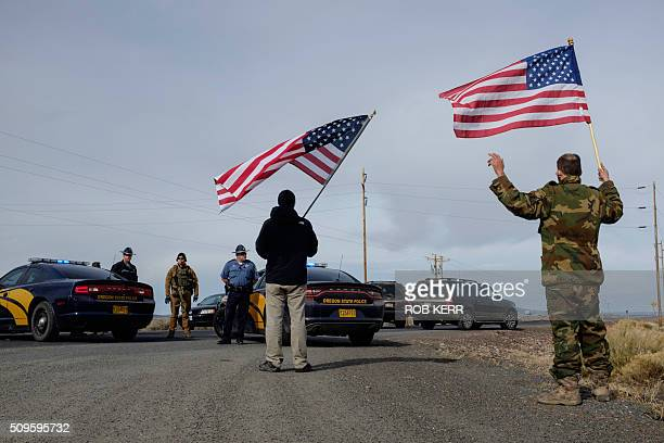 Supporters of the movement agains the federal government carry US flags and approach the FBI and Oregon State Police near the Malheur Wildlife Refuge...