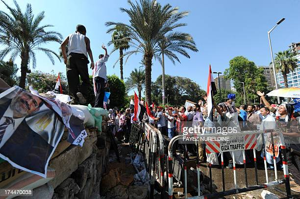 Supporters of the Muslim Brotherhood and Egypt's ousted president Mohamed Morsi carry his portrait as they demonstrate near Cairo university on July...