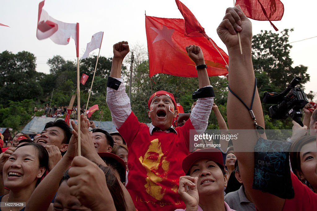 Supporters of the National League for Democracy celebrate preliminary election results coming from the regions in front of the party office on April...