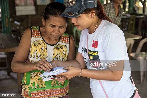 Supporters of the National League for Democracy democracy icon Aung San Suu Kyi's party explain to villagers how to rightly stamp a voting bulletin...
