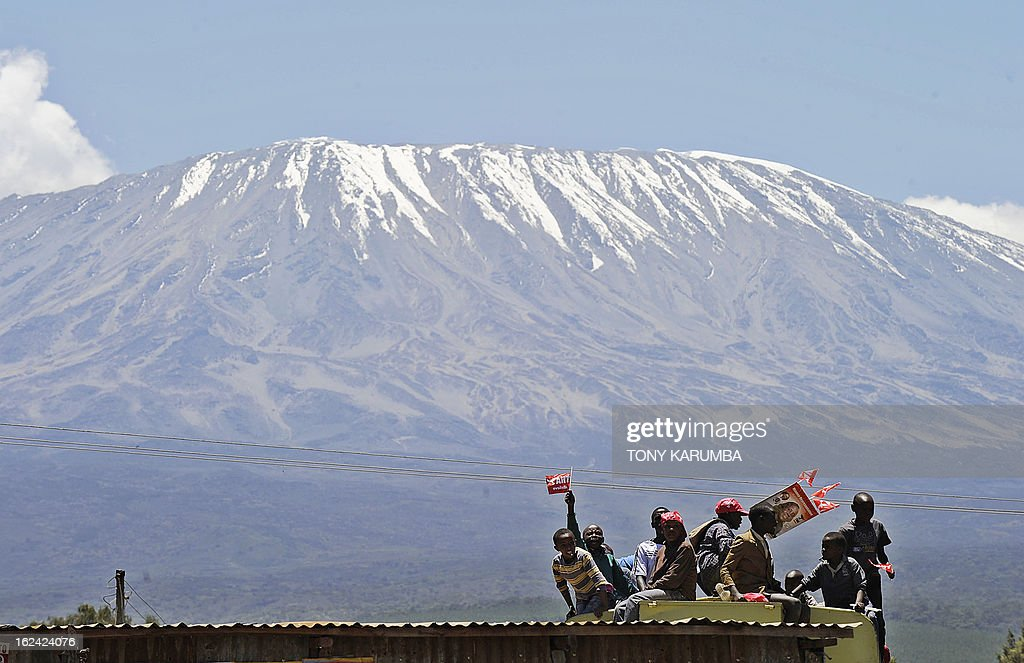 Supporters of the Nationaql Alliance, TNA presidential candidate Uhuru Kenyatta sit atop a lorry on February 23, 2013 at Oloitokitok, near the Tanzanian border as they attend a political rally at the border town at the foot of Africa's highest mountain, Kilimanjaro. AFP PHOTO/Tony KARUMBA