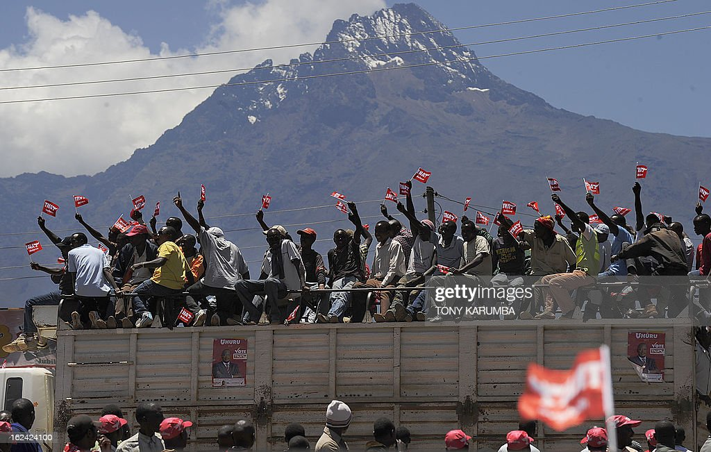Supporters of the Nationaql Alliance, TNA presidential candidate Uhuru Kenyatta, sit atop a lorry on February 23, 2013 at Oloitokitok, near the Tanzanian border as they attend a political rally at the border town at the foot of Africa's highest mountain, Kilimanjaro. AFP PHOTO/Tony KARUMBA
