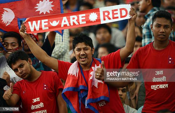 Supporters of the Nepalese national team cheer prior to a SAFF Championships football match Nepal vs Pakistan on September 3 2013 The game ended in a...