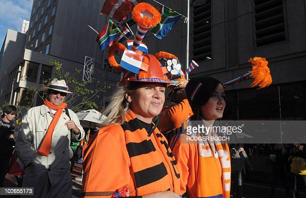 Supporters of The Netherlands wearing makarapas decorated with the national colours walks through the centre of the city with thousands of Dutch...