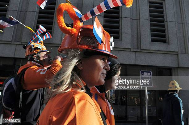 Supporters of The Netherlands wearing makarapas decorated with the national colours walk through the centre of the city with thousands of Dutch...