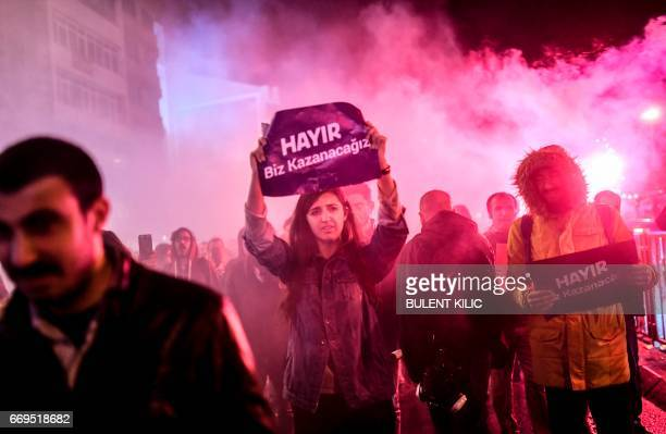 TOPSHOT Supporters of the 'No' hold leaflets reading 'no' as they gather at the Kadikoy district in Istanbul on April 17 2017 to protest following...