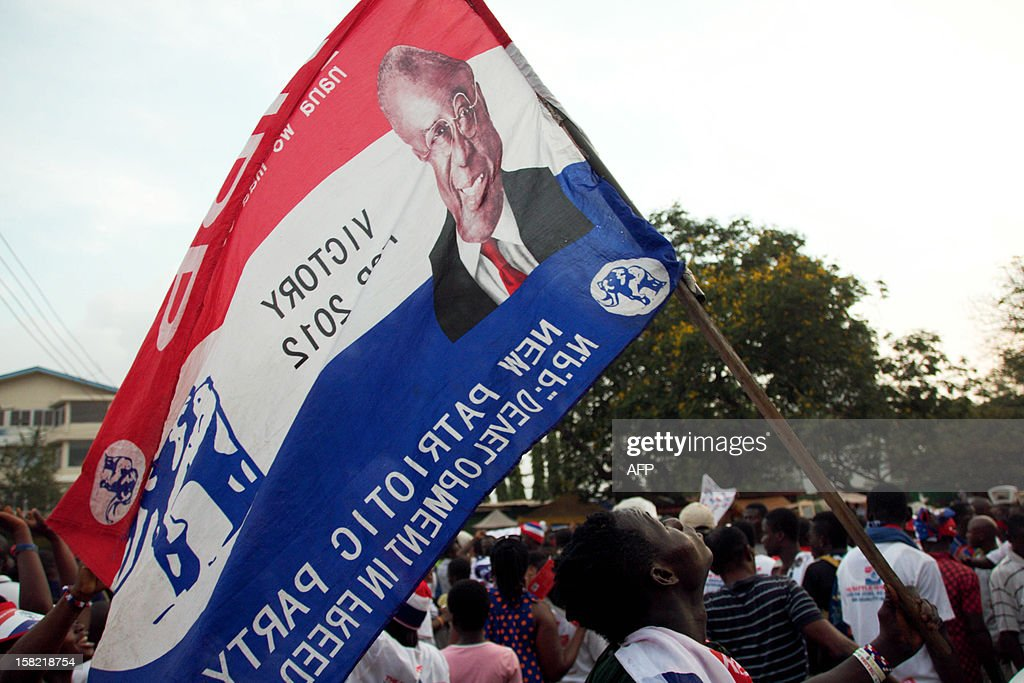 A supporters of the opposition New Patriotic Party waves a flag with a picture of presidential candidate of the New Patriotic Party Nana AkufoAddo at...