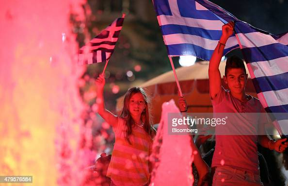 Supporters of the 'OXI' or 'No' vote wave Greek national flags outside the parliament on Syntagma square as early results show them ahead in the...