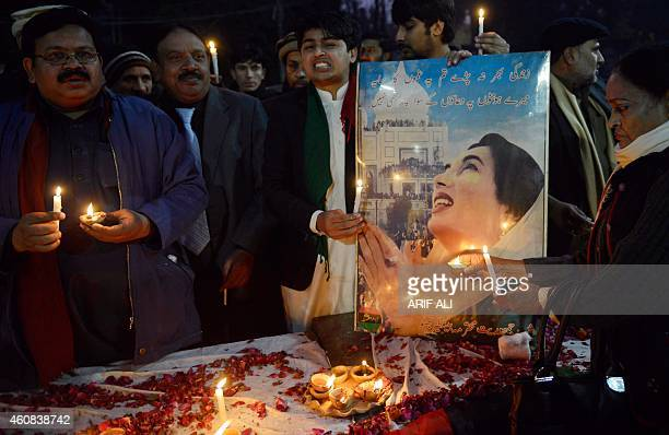 Supporters of the Pakistan Peoples Party hold candles during a rally in Lahore on December 26 2014 to commemorate the seventh death anniversary of...