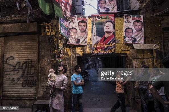 Supporters of the Pakistan Tehrik e Insaf party mingle in the street as banners show images of party chairman Imran Khan in an alley way in the Old...