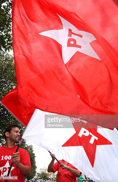 Supporters of the party of Luiz Inacio Lula da Silva president of Brazil wave flags near a polling place in So Bernado do Campo near Sao Paulo Brazil...