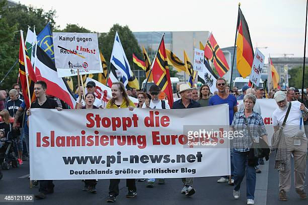 Supporters of the Pegida movement carry a banner that reads 'Stop the Islamization of Europe' as they march past the Chancellery on August 24 2015 in...