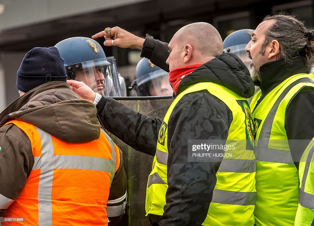 Supporters of the Pegida movement (Patriotic Europeans Against the Islamisation of the Occident) confront policemen during a demonstration in Calais, northern France on February 6, 2016. Anti-migrant protesters in the French port city of Calais clashed with police as they defied a ban and rallied in support of a Europe-wide initiative by the Islamophobic Pegida movement. / AFP / PHILIPPE HUGUEN