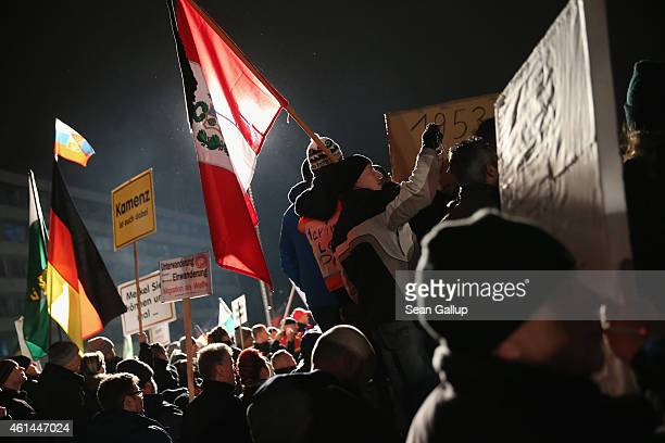 Supporters of the Pegida movement gather before strolling through the city center during their weekly protest on January 12 2015 in Dresden Germany...