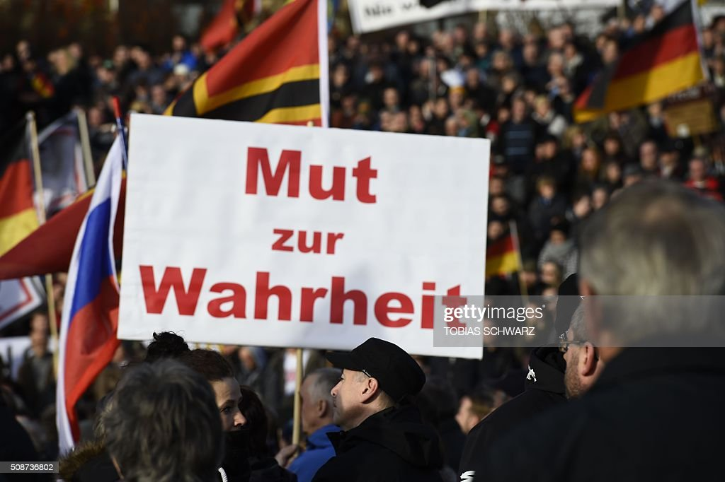 Supporters of the Pegida movement (Patriotic Europeans Against the Islamisation of the Occident) hold a placard which reads 'courage for truth' in Dresden, eastern Germany, on February 6, 2016. / AFP / TOBIAS SCHWARZ