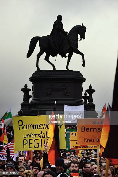 Supporters of the Pegida movement hold banners during their weekly demonstration on January 25 2015 in Dresden Pegida is an acronym for 'Patriotische...