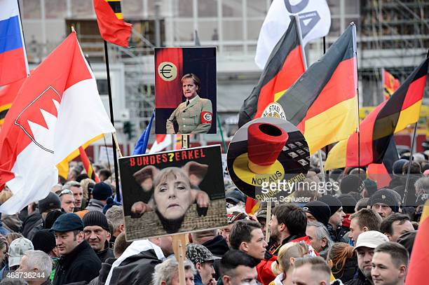 Supporters of the Pegida movement hold placards during a weekly protest on Easter Monday on April 6 2015 in Dresden Germany The Pegida movement which...