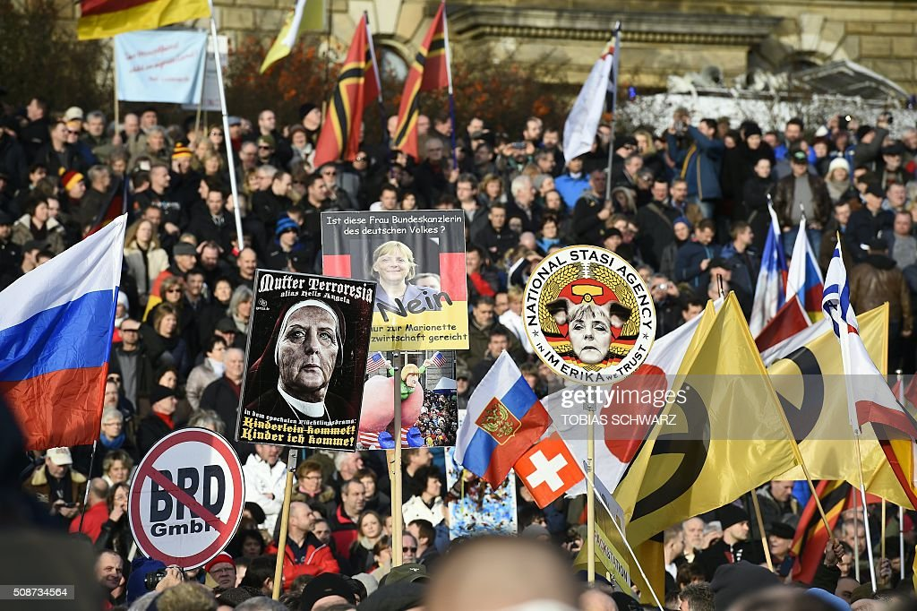 Supporters of the Pegida movement (Patriotic Europeans Against the Islamisation of the Occident) hold placards featuring Angela Merkel in Dresden, eastern Germany, on February 6, 2016. Fet / AFP / TOBIAS SCHWARZ