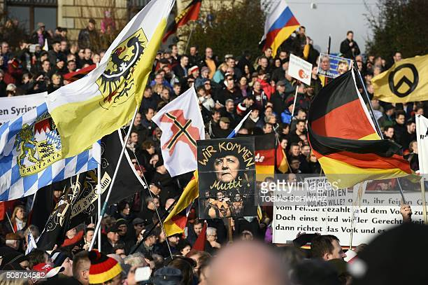 Supporters of the Pegida movement hold placards featuring Angela Merkel in Dresden eastern Germany on February 6 2016 / AFP / TOBIAS SCHWARZ
