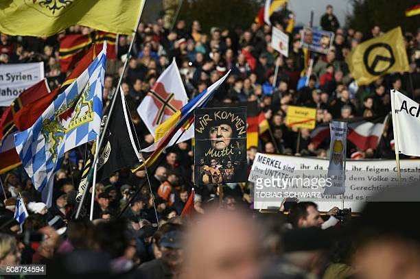 Supporters of the Pegida movement hold placards featuring Angela Merkel in Dresden eastern Germany on February 6 2016 Fet / AFP / TOBIAS SCHWARZ