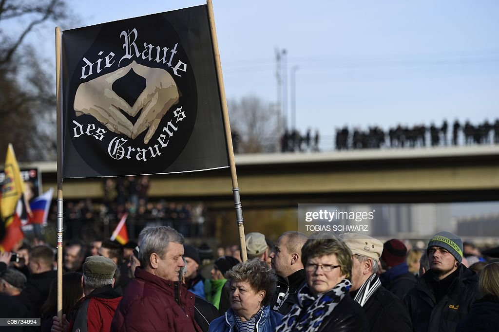 Supporters of the Pegida movement (Patriotic Europeans Against the Islamisation of the Occident) hold placards featuring Angela Merkel, on February 6, 2016, in Dresden, eastern Germany. / AFP / TOBIAS SCHWARZ