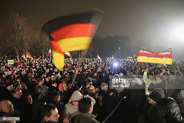 Supporters of the Pegida movement hold up German flags at another of their weekly gatherings on January 5 2015 in Dresden Germany Pegida is an...