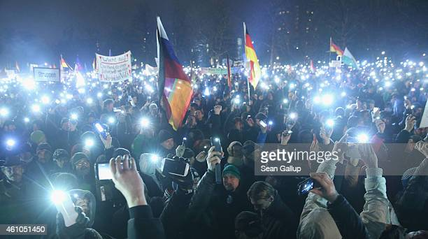 Supporters of the Pegida movement hold up their smartphones at the conclusion of another of their weekly gatherings on January 5 2015 in Dresden...