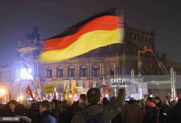 Supporters of the Pegida movement including one man waving a German flag gather on the first anniversary since the first Pegida march on October 19...