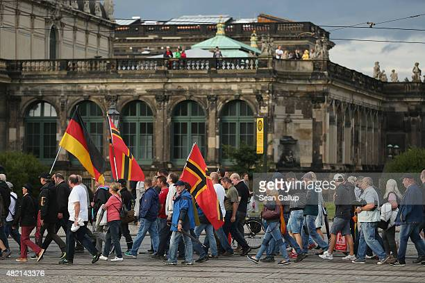Supporters of the Pegida movement march past the Zwinger art museum during their weekly gathering on July 27 2015 in Dresden Germany A Pegida leader...