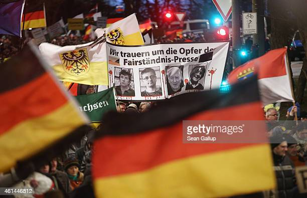 Supporters of the Pegida movement march with a banner showing murdered Charlie Hebdo employees to show their solidarity with the victims of the...