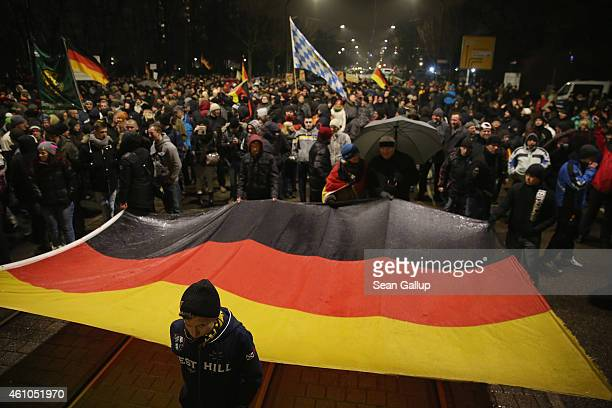 Supporters of the Pegida movement march with a giant German flag at another of their weekly protests on January 5 2015 in Dresden Germany Pegida is...