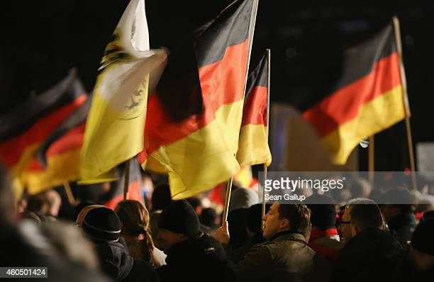 Supporters of the Pegida movement march with German flags at another of their weekly gatherings on December 15 2014 in Dresden Germany Pegida is an...
