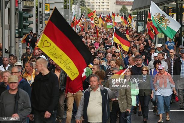 Supporters of the Pegida movement march with German flags during their weekly gathering on July 27 2015 in Dresden Germany A Pegida leader spoke out...