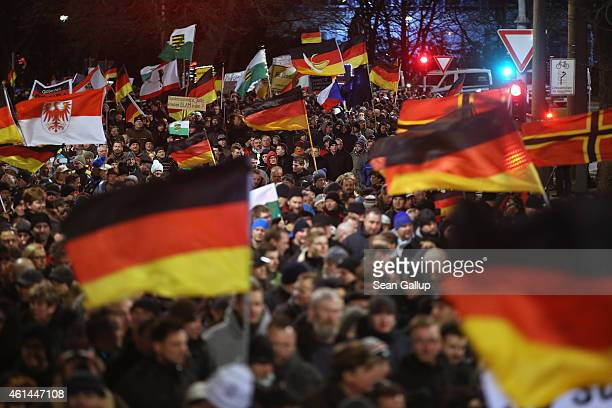 Supporters of the Pegida movement wave German and other flags while strolling through the city center during their weekly protest on January 12 2015...
