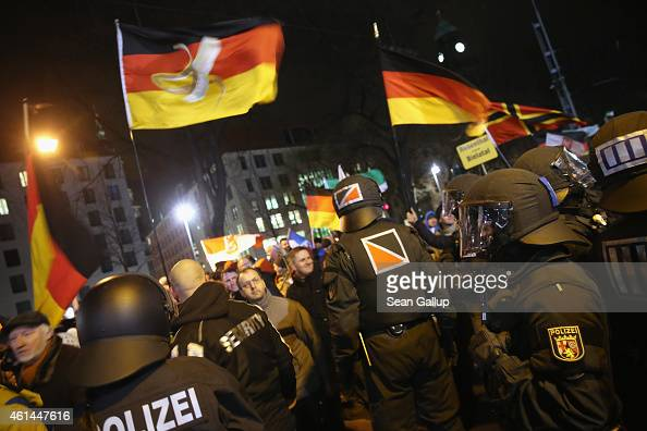 Supporters of the Pegida movement wave German while strolling past riot police through the city center during their weekly protest on January 12 2015...