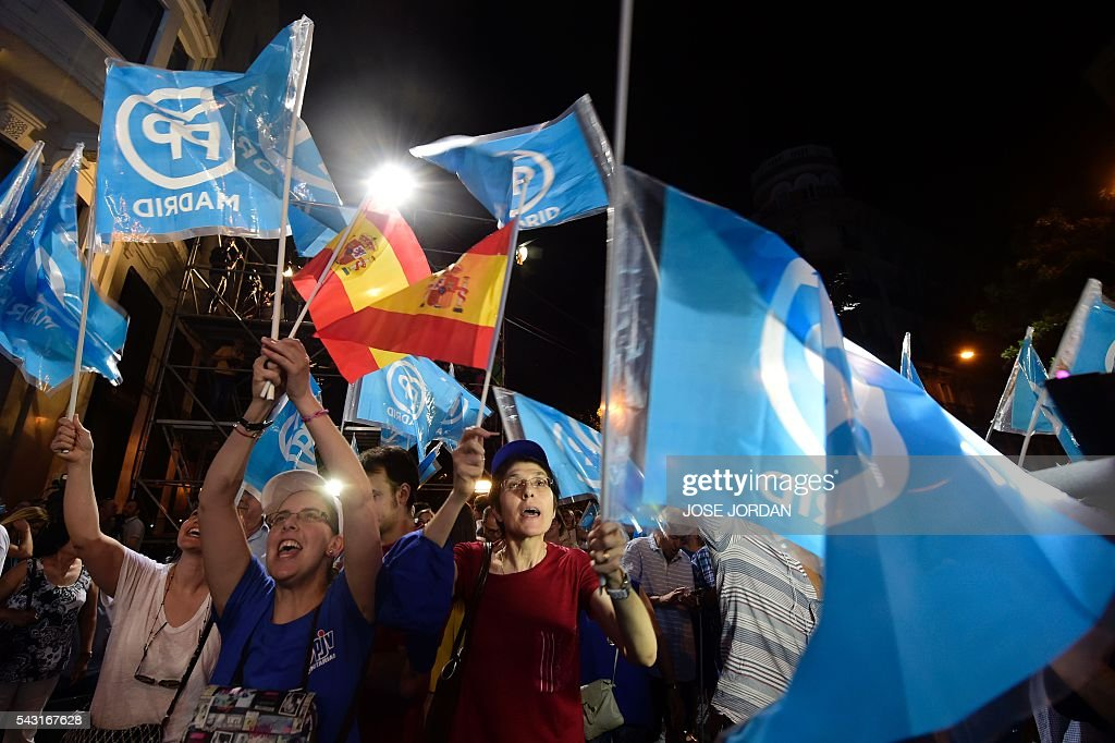 Supporters of the Popular Party (PP) hold flags as they wait outside the PP headquarters during Spain's general election in Madrid on June 26, 2016. Spain's second elections in six months was due to conclude on June 26 in much the same way as they did in December, with the incumbent conservatives winning tailed by the Socialist party, partial results showed. / AFP / JOSE