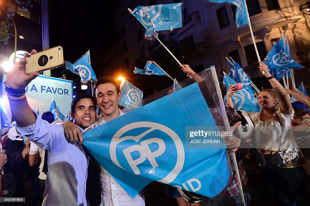 Supporters of the Popular Party (PP) pose for a selfie as they wait outside the PP headquarters during Spain's general election in Madrid on June 26, 2016. Spain's second elections in six months was due to conclude on June 26 in much the same way as they did in December, with the incumbent conservatives winning tailed by the Socialist party, partial results showed. / AFP / JOSE