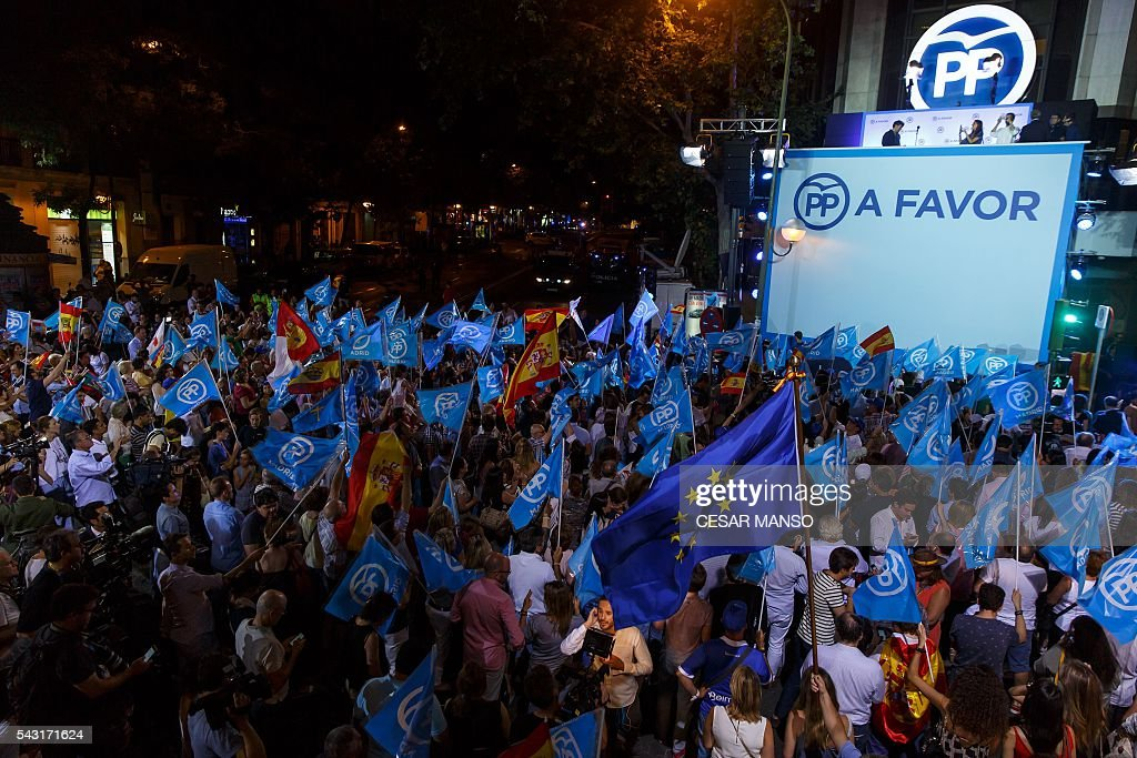 Supporters of the Popular Party (PP) wave flags as they wait for results outside the PP headquarters during Spain's general election in Madrid on June 26, 2016. Spain's second elections in six months was due to conclude on June 26 in much the same way as they did in December, with the incumbent conservatives winning tailed by the Socialist party, partial results showed. / AFP / CESAR