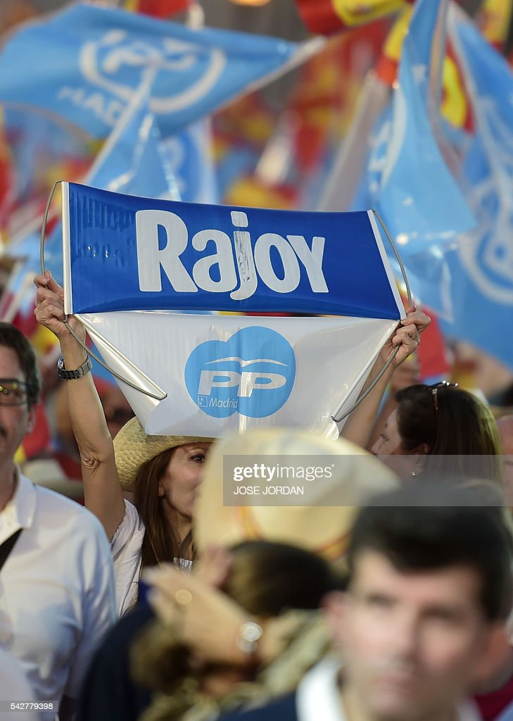 Supporters of the Popular's Party (PP) waves Spanish and part flags during the partys final campaign meeting in Madrid on June 24, 2016 ahead of the June 26 general election. Spain votes again on June 26, six months after an inconclusive election which saw parties unable to agree on a coalition government. JORDAN