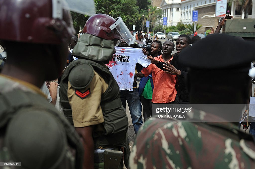 Supporters of the Raila Odinga led CORD alliance confront the police while displaying a bloodied shirt on March 16, 2013, outside Kenya's supreme court building, that belonged to one of them who was injured by a tear gas canister fired by police at youth who had gathered to express support for a petition challenging the outcome of Kenya's general election. Kenya's outgoing Prime Minister Raila Odinga, who was narrowly defeated in presidential polls by Uhuru Kenyatta, filed a formal challenge Saturday against the result. Officials from Odinga's Coalition for Reform and Democracy (CORD) filed the suit at the Supreme Court after Odinga spoke to supporters and journalists in front of his offices. AFP PHOTO/Tony KARUMBA